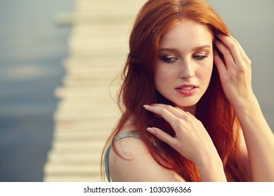 summer portrait of a young redhead woman on background of water in countryside