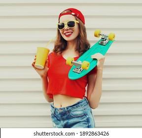 Sommerporträt einer jungen Lächlerin mit grünem Skateboard mit roter Baseballkappe auf weißem Hintergrund