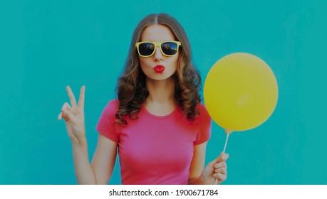 Sommerporträt einer jungen Frau, die sich mit gelbem Ballon auf blauem Hintergrund die Lippen bläst