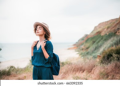 Summer portrait of young woman in brown hat having fun on the sea.outdoor.slim beautiful woman,bohemian outfit,indie style,summer vacations,positive,romantic,girl in a dress,attractive,dreamer,bag,joy
