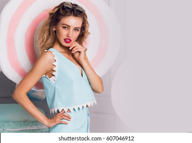 Summer positive portrait of young cheerful girl in stylish blue  playsuit posing on fake sweets and  lollipop background. Confectionery style. Space for text.
