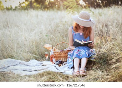 Summer - Provencal picnic in the meadow.  girl sitting reading a book and near a picnic basket and baguette, wine, glasses, grapes and rolls