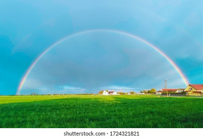 Summer rainbow landscape. Houses and field in the countryside in the background.