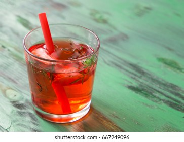 Summer refreshing cocktail with strawberry, ice and thyme on a light green wooden table. space for text