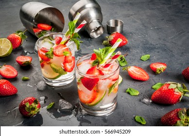Summer refreshing mojito cocktail with strawberry, mint and lime, on a dark gray stone (concrete) table with shaker for whipping drinks, copy space