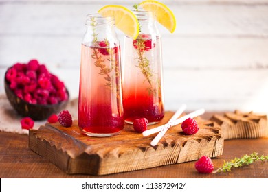 Summer refreshing non-alcoholic cocktails. Fruit drinks. Raspberry homemade lemonade with fresh organic rosemary and lemon. On a white wooden table. Copy space.