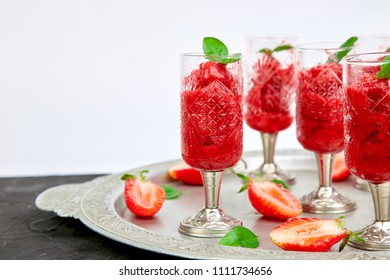 Summer refreshing strawberry sorbet, slush granita drink in serving glasses on silver tray. Healthy low calorie summer treat, dessert. Iced Cocktail on black  background.