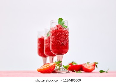 Summer refreshing strawberry sorbet, slush granita drink in serving glasses. Healthy low calorie summer treat, dessert. Iced Cocktail on pink background