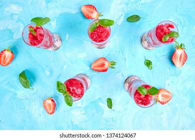 Summer refreshing strawberry sorbet, slush granita drink in serving glasses. Healthy low calorie summer treat, dessert. Iced Cocktail on blue background. Flat lay