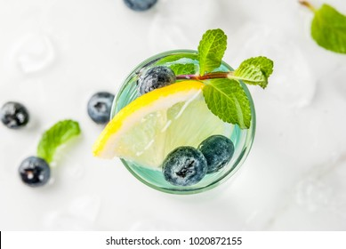 Summer refreshment drinks, Blueberry Lemonade or mojito cocktail with lemon, fresh blueberries and mint, white marble background copy space top view