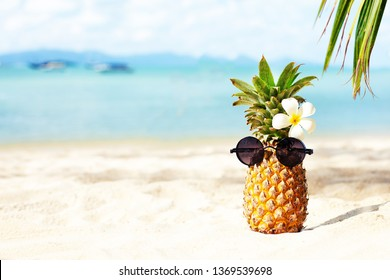 summer relax concept background with Pineapple in glasses on the beach