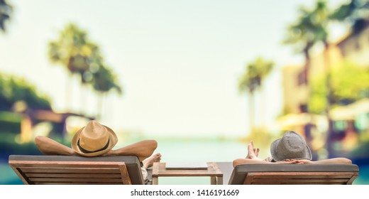 Summer resort hotel stay relaxation with tourist traveller couple take it easy happily resting on beach chair on holiday travel vacation poolside peacefully at tropical beach house swimming pool