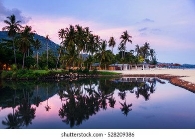 Summer resort at Ko Samui, Thailand. Little bungalow hidden in the trees with water at sunset