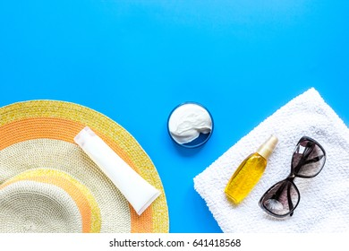 Summer rest with protiction cream, hat, towel blue desk top view space for text