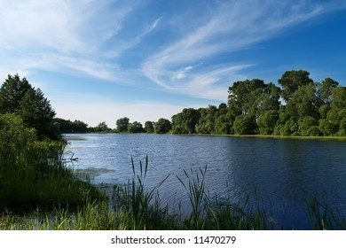 Summer river bank view with blue sky and light clouds