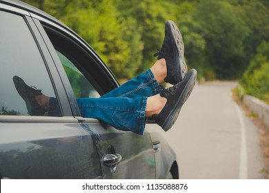 Summer road trip car vacation concept. Woman legs out the windows in car above the road in forest. Conceptual freedom, travel and holidays image with copy space.
