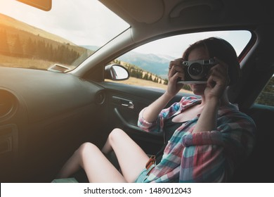 Summer Road Trip. Girl with retro camera taking pictures from the car window.