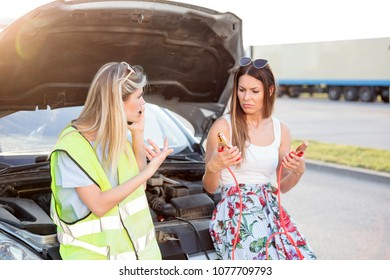 Summer road trip gone wrong. Two young women stranded by the broken car, calling for help.