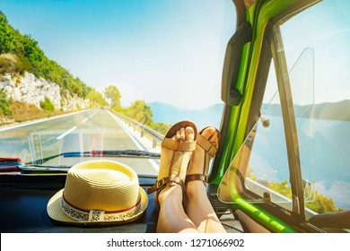 Summer road trip with young female legs on dashboard inside of classic oldtimer van cruising alongside sea coast