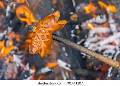 Summer roasting of sausages on fire. Holiday in the countryside. Preparation of food on fire