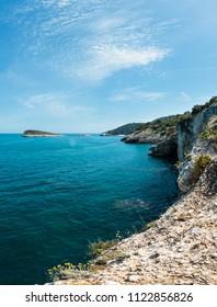 Summer rocky sea coast Baia Di Campi Vieste and isola di Campi on the Gargano peninsula, Puglia, Italy