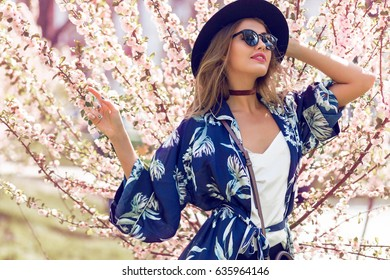 Summer  romantic  image of  stylish casual woman in sunglasses and hat , trendy silk blouse and fashionable accessories . positive mood. Pretty girl walking.