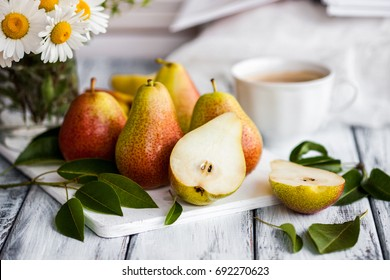 Summer romantic still life. Fresh ripe organic Pears, bouquet of field daisy flowers, cup of coffee, book. Shabby chic style high key photo. White table surface for background. Natural healthy lunch.