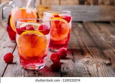Summer Rose cocktail. Sparkling Lemon Raspberry Lemonade Sangria in glass on wooden background