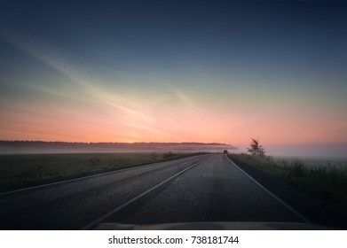 summer rural landscape with blue and red sky, fog and the road. sunrise.