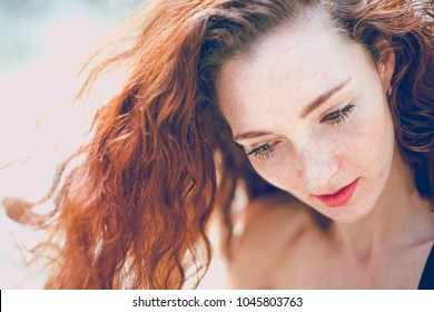 Summer sad portrait, beautiful freckled young adult girl with red hair look down. Cute curly redhead woman dreaming or thinking against outdoor background. beauty fashion redhead woman