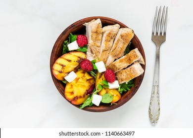 summer salad with grilled chicken and peach, feta cheese and raspberries in a bowl with fork. healthy food. top view