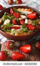 Summer salad with strawberries, grilled chicken, brie and arugula close-up on the table. vertical