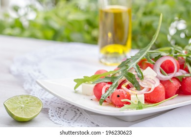 Summer salad with watermelon, feta cheese, onion rings, lime juice, olive oil and rucola. Selective focus.