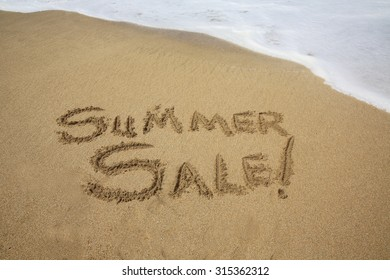 Summer sale, a message written in the sand at the beach.