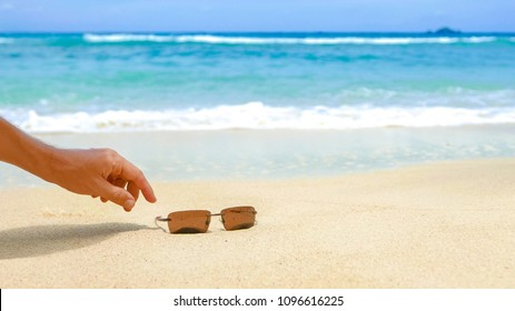 Summer sale vacation background, person points the sunglasses on pristine tropical beach