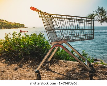 Summer sale vacations. View from above of beach, sunny day, seacoast, sailboat  and closeup empty shopping cart.
