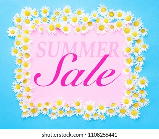 Summer Sale written on pink and blue background with white daisies