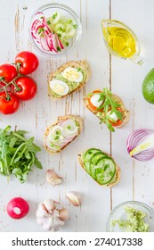 Summer sandwiches ingredients - avocado, cucumber, radish, tomato, mozzarella and eggs, white wood background, top view