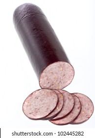 Summer sausage sliced and isolated on white.