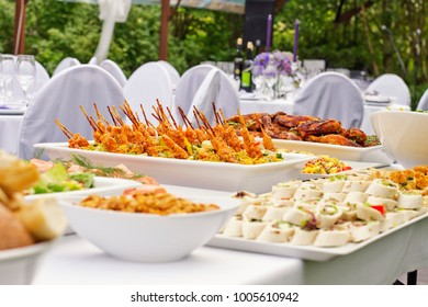Summer Scandinavian style outdoor wedding party in old abandoned greenouse. White table with various snacks.