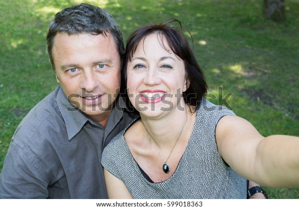 Summer scene of a beautiful couple forties takes a photo selfie in a park with joy and love