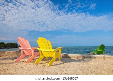 Summer scene with colorful lounge chairs on a tropical beach in Florida with blue sky and ocean
