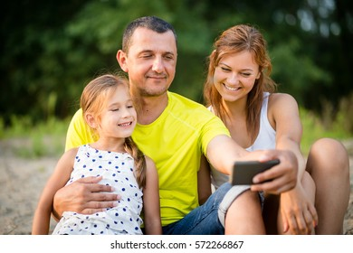 Summer scene of a father with daughters taking selfie with his smartphone