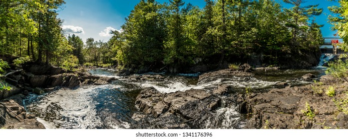 Summer scene featuring River rapids, water flowing through rocks and rock crevices, details on rock geology showing dark patina on rock around River bed on a sunny summer day