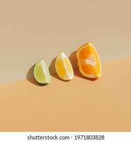 Summer scene with fresh slices of tropical citrus fruit on sandy colored background. Minimal aesthetic.
