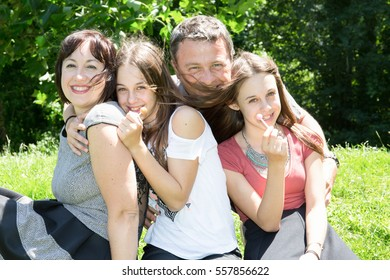 Summer scene of Happy family at the park with father mother and twin sister