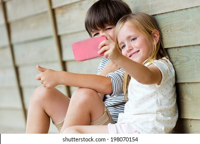 Summer scene of Happy young brothers taking selfies with her smartphone in the park