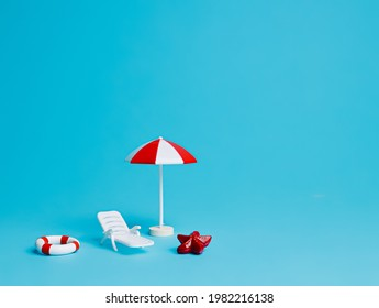 Summer scene with parasol, sunbed, and swim ring isolated on light blue background. Creative vacation concept. Beach, pool or travel idea.