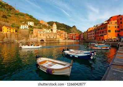 Summer scene of Vernazza, one of the five seaside villages in Cinque Terre, Italy, with a church tower among colorful houses bathed in warm sunlight & boats parking in the harbor on a sunny afternoon