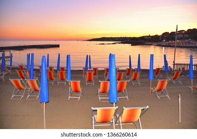 summer scene with warm colorful sunset on empty beach with closed blue umbrellas and orange chairs in Versilia, Tuscany, Italy
